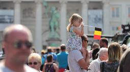Seorang anak kecil memegang bendera nasional ketika melihat parade selama perayaan Hari Nasional Belgia di Brussels, Kamis (21/7). Belgia dalam status waspada sejak tragedi Bom Brussels yang menewaskan 34 orang pada 22 Maret 2016 lalu. (Foto: Arie Asona)