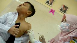 Ekspresi siswa MIN Ulee Kareng saat mendapat vaksinasi anti virus difteri di Banda Aceh, Aceh, Selasa (20/2). Maraknya kasus difteri belakangan ini membuat Kemenkes menginstruksikan pemberian vaksin untuk usia 1 hingga 19 tahun. (CHAIDEER MAHYUDDIN/AFP)