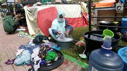 Pengungsi korban gempa dan tsunami Palu mencuci pakaian di tenda pengungsian lapangan Walikota Palu, Sulawesi Tengah, Senin (8/10). Pemerintah tengah menentukan lokasi yang tepat untuk membangun hunian sementara bagi korban. (Liputan6.com/Fery Pradolo)