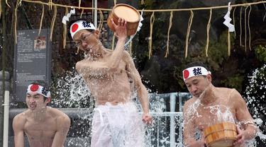 Penganut Shinto setengah telanjang menuangkan air dingin ke tubuhnya saat festival ketahanan dingin tahunan di Kuil Kanda Myojin Shinto, Tokyo, Jepang, Sabtu (18/1/2020). Menyiramkan air dingin ke tubuh diyakini dapat memurnikan jiwa mereka. (AP Photo/Eugene Hoshiko)