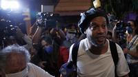 Awak media mengambil gambar mantan pemain timnas Brasil, Ronaldinho setibanya di sebuah hotel untuk menjalani tahanan rumah di Asuncion, Selasa (7/4/2020). Ronaldinho dan kakaknya dijebloskan ke penjara pada 5 Maret 2020 lantaran menggunakan paspor palsu saat masuk ke Paraguay. (AP/Jorge Saenz)