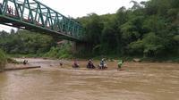 Jembatan sepanjang kurang lebih 50 meter ini ditutup karena sedang diperbaiki. Warga pun terpaksa menyeberang dengan rakit bambu meskipun arusnya deras dan dalam. (Liputan6.com/Darno)