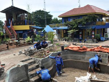 Petugas dari Dinas Sumber Daya Air (SDA) Bidang Aliran Tengah saat menyelesaikan pembangunan Taman Robika di Pintu Air Manggarai, Jakarta, Kamis (14/3). (merdeka.com/Iqbal S. Nugroho)