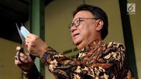 Mendagri Tjahjo Kumolo mengunting E-KTP di gudang penyimpanan barang inventarisasi Kemendagri di Jalan Raya Parung, Kab Bogor (30/5). Tjahjo melihat kondisi gudang pasca-insiden tercecernya E-KTP di jalan raya Selabenda Bogor. (Merdeka.com/Arie Basuki)