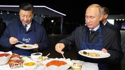 Presiden Rusia Vladimir Putin (kanan) dan Presiden China Xi Jinping (kiri) menyantap pancake buatan bersama di sela acara Eastern Economic Forum di Vladivostok, Rusia, Selasa (11/9). (Sergei Bobylev/TASS News Agency Pool Photo via AP)