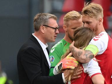 Bersama kiper Timnas Denmark, Kasper Schmeichel, Kjaer pun kemudian mencoba menenangkan Sabrina Kvist Jensen dengan memeluknya. (Foto: AFP/Pool/Jonathan Nackstrand)