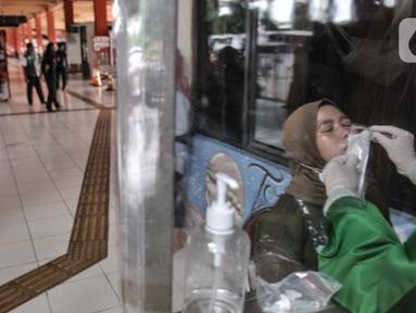 Penumpang mengikuti tes rapid antigen saat tiba di Terminal Kampung Rambutan, Jakarta, Minggu (3/1/2021). Pengelola Terminal Kampung Rambutan menyediakan tes antigen bagi penumpang yang baru tiba jika tidak memiliki surat kesehatan dengan harga Rp150 ribu per orang. (merdeka.com/Iqbal S. Nugroho)