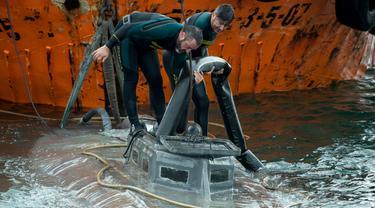 Penyelam dari anggota Garda Sipil Spanyol memeriksa kapal selam di perairan Aldan, Spanyol (26/11/2019). Kepolisian Spanyol menyita kapal selam berukuran 20 meter bermuatan berton-ton kokain asal Amerika Selatan di lepas pantai wilayah barat laut Galicia. (AFP/Lalo R. Villar)