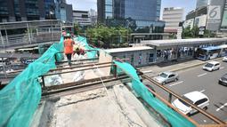 Pekerja membongkar jembatan penyeberangan orang (JPO) Tosari, Jakarta, Minggu (16/12). JPO Tosari akan digantikan oleh pelican crossing. (Merdeka.com/Iqbal Nugroho)