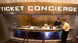 Pengunjung bioskop memakai masker untuk membantu mencegah penyebaran Covid-baru penyebab Covid-19 ketika ia membeli tiket di bioskop Paragon Cineplex di Bangkok, Thailand, Senin (1/6/2020).  Kebijakan itu menyusul penurunan jumlah kasus penularan Covid-19. (AP Photo/Sakchai Lalit)