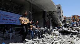 Seorang penyanyi Palestina tampil selama acara musik di puing-puing bangunan yang baru-baru ini hancur oleh serangan udara Israel di kota Gaza, Selasa (14/5/2019). Aksi tersebut untuk menyerukan pemboikotan terhadap Kontes Lagu Eurovision 2019 yang diselenggarakan di Israel. (REUTERS/Mohammed Salem)
