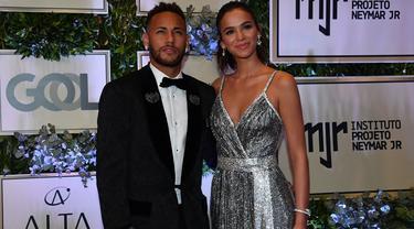 Pemain PSG, Neymar, didampingi sang kekasih, Bruna Marquezine, saat menghadiri acara amal untuk Institut Neymar Jr di Sao Paulo, Brasil, Kamis (19/7/2018). Bintang asal Brasil itu tampak menawan dengan balutan jas. (AFP/Nelson Almeida)