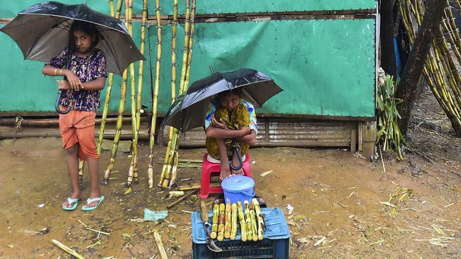Dua anak perempuan pengungsi Rohingyah menjual tebu musim hujan di kamp pengungsi Kutupalong di Ukhia (12/9/2019). Kamp ini adalah salah satu dari dua kamp pengungsi yang dikelola pemerintah di Cox's Bazar, kamp yang satunya lagi adalah kamp pengungsi Nayapara. (AFP Photo/Munir Uz Zaman)