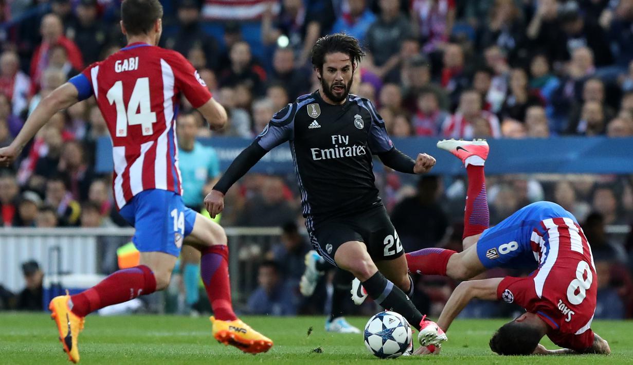 Gelandang Real Madrid, Isco berusaha melewati dua pemain Atletico Madrid di leg kedua semifinal Liga Champions di Stadion Vicente Calderon, Spanyol (10/5). Real Madrid melaju ke final usai menang dengan aggregat 4-2. (AFP Photo/Cesar Manso)