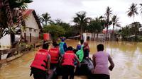 Warga yang berada di lokasi terisolir karena banjir, diantar dengan perahu karet menuju TPS. 9Liputan6.com/Ahmad Akbar)