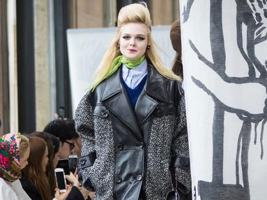 Aktris Elle Fanning memperagakan busana karya Miu Miu pada pagelaran Paris Fashion Week Fall-Winter 2018, Selasa (6/3). Adik dari Dakota Fanning ini memakai coat abu-abu berbahan kulit dengan cutting besar. (Vianney Le Caer/Invision/AP)