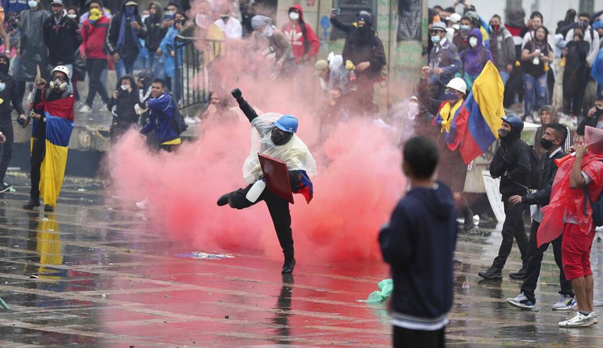 Seorang pengunjuk rasa antipemerintah mengembalikan tabung gas air mata ke polisi saat bentrokan di Bogota, Kolombia, Rabu (5/5//2021). Protes menentang proposal reformasi pajak terus berlanjut meski Presiden Ivan Duque telah mencabutnya. (AP Photo/Fernando Vergara)