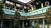 Petugas keamanan melintasi ruangan kelas usai kebakaran melanda SMA Negeri 100 Jakarta, Rabu (1/7/2020). Beruntung tidak ada korban jiwa dalam kebakaran ini, namun sedikitnya tujuh ruangan beserta isinya ludes dilalap si jago merah. (merdeka.com/Iqbal S Nugroho)