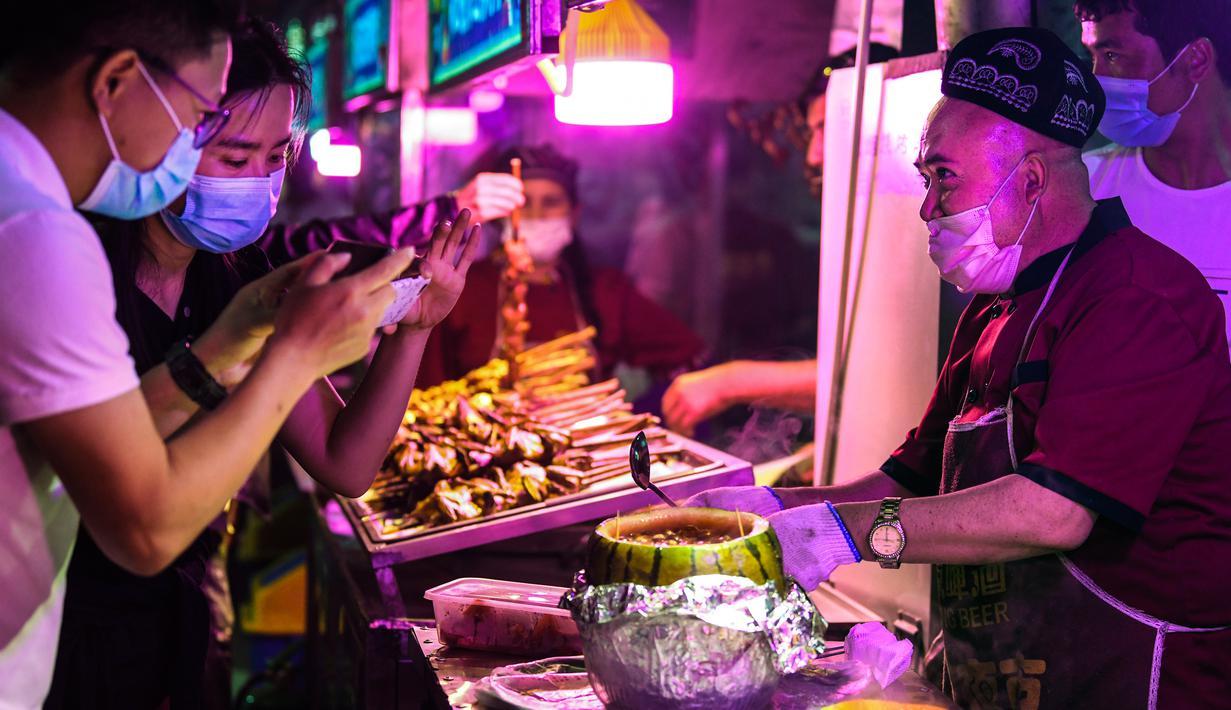 Seorang pedagang menyajikan hidangan lokal kepada para pelanggan di sebuah pasar malam di Hotan, Daerah Otonom Uighur Xinjiang, China barat laut, pada 18 Mei 2020. Seiring cuaca mulai menghangat, aktivitas pariwisata lokal pun perlahan kembali pulih. (Xinhua/Wang Fei)