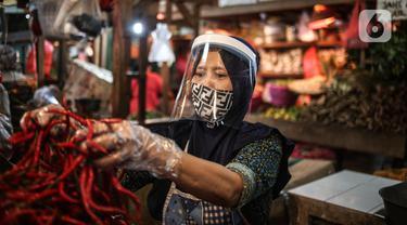 Salah satu pedagang menggunakan face shield dan sarung tangan saat melayani pembeli di Pasar Senen, Jakarta, Senin (1/6/2020). Kementerian Perdagangan menyiapkan pedoman bagi penyelenggara kegiatan perdagangan untuk diterapkan pada saat kenormalan baru (new normal). (Liputan6.com/Faizal Fanani)