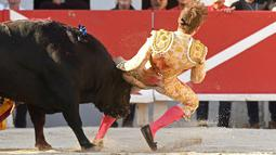 Tanduk banteng Spanyol Jandilla tepat mengenai bagian belakang matador dari Prancis Andy Younes saat kompetis Feria du Riz di Arles, Prancis (4/1). (AFP/Boris Horvat)