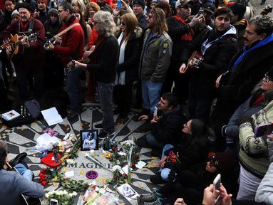 Sejumlah orang, penggemar dari grup band The Beatles berkumpul sambil bernyanyi saat memperingati 36 tahun kematian John Lennon di New York, AS (8/12). Mereka berkumpul di sebuah tempat yang bernama Strawberry Fields. (Reuters/Mark Kauzlarich)