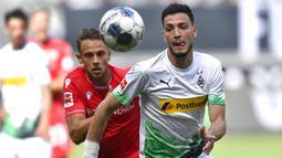 Pemain Borussia Moenchengladbach, Ramy Bensebaini, berebut bola dengan pemain Union Berlin, Marcus Ingvartsen, pada laga Bundesliga di Stadion Borussia-Park, Minggu (31/5/2020). Moenchengladbach menang 4-1 atas Union Berlin. (AP/Martin Meissner)