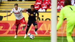 Gelandang RB Leipzig, Christopher Nkunku, berebut bola dengan pemain Koln, Benno Schmitz, pada laga Bundesliga di Stadion Rhein Energie, Senin (1/6/2020). RB Leipzig menang dengan skor 4-2. (AP/Ina Fassbender)
