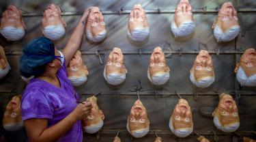 Pekerja menggantungkan topeng lateks calon Presiden Meksiko Andres Manuel Lopez Obrador, dari partai MORENA, di Rev, sebuah pabrik di Cuernavaca, Morelos State, Meksiko, (28/3). Meksiko akan mengadakan Pemilu pada 1 Juli 2018. (AFP Photo/Alfredo Estrella)