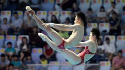 Aksi atlet loncat indah China, Lian Junjie dan Si Yajie saat tampil pada babak final platform sinkronisasi 10 meter campuran di Kejuaraan Renang Dunia, Gwangju, Korea Selatan, Sabtu (13/7/2019). (AP Photo/Lee Jin-man)