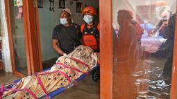 Relawan dan keluarga mengevakuasi jenazah warga lansia saat banjir melanda kawasan Cipinang Melayu, Jakarta Timur, Jumat (19/2/2021). Seorang nenek (80) meninggal di kediamannya, di lokasi banjir, di RW 04, kawasan tersebut karena sakit dan sudah lanjut usia. (Liputan6.com/Herman Zakharia)