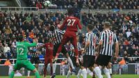 Striker Liverpool, Divock Origi, bersiap melakukan sundulan saat melawan Newcastle pada laga Premier League di Stadion St James Park, Newcastle, Sabtu (5/5). Newcastle kalah 2-3 dari Liverpool. (AFP/Lindsey Parnaby)