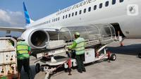 Petugas kargo memasukkan kontainer berisi empat orangutan Sumatera diselamatkan dari pemeliharaan illegal dan Kalimantan berkelamin betina bernama Ucokwati dan Mungil ke dalam bagasi pesawat Garuda Indonesia Airbus A330-300 (GA215) di Bandara Yogyakarta (12/04/2021). (Liputan6.com/Pool/GIA)