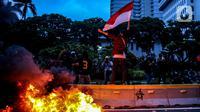 Sejumlah pendemo berswafoto di kobaran api saat aksi unjuk rasa di kawasan patung kuda, Jakarta, Selasa (20/10/2020). Gelombang protes tolak UU Cipta Kerja belum surut sejak beleid kontoversial itu disahkan pemerintah dan DPR pada 5 Oktober lalu. (Liputan6.com/Faizal Fanani)