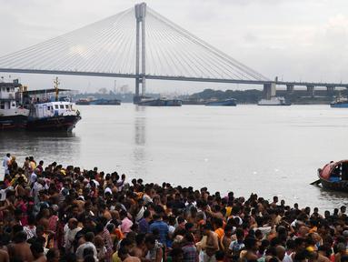 Ratusan umat Hindu melakukan ritual 'Tarpan' mempersembahkan doa kepada leluhur mereka pada hari terakhir Pitrupaksh di tepian Sungai Gangga di Kolkata (19/9). Dalam mitologi Hindu Hari Pitrupaksh juga disebut 'Mahalaya'. (AFP Photo/Dibyangshu Sarkar)