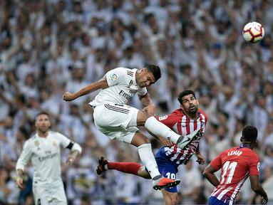 Gelandang Real Madrid, Casemiro, duel udara dengan striker Atletico Madrid, Diego Costa, pada laga La liga di Stadion Santiago Bernabeu, Madrid, Sabtu (29/9/2018). Kedua klub bermain imbang 0-0. (AFP/Oscar Del Pozo)