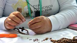 Seorang narapidana di penjara Wanita Virgen de Fatima membuat rosario kayu di Lima, Peru (12/1). Penjara Virgen de Fatima hanyalah satu dari 12 lembaga pemasyarakatan yang membuat rosario untuk kunjungan Paus Fransiskus. (AFP Photo/Cris Bouroncle)