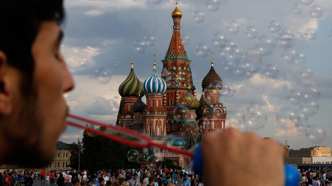 Seorang pria meniup gelembung di Lapangan Merah jelang final Piala Dunia 2018 antara Prancis melawan Kroasia di Moskow, Rusia, (13/7).  (AP Photo/Rebecca Blackwell)#source%3Dgooglier%2Ecom#https%3A%2F%2Fgooglier%2Ecom%2Fpage%2F%2F10000