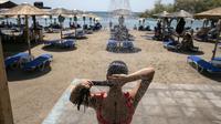 Seorang wanita mandi di pantai Desa Lagonissi, beberapa mil barat daya Athena, Yunani, Kamis (29/7/2021). Gelombang panas membuat orang-orang berbondong-bondong ke pantai, air mancur umum, dan lokasi ber-AC. (AP Photo/Yorgos Karahalis)