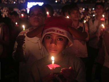 """Seorang bocah laki -laki membawa lilin saat mengikuti perayaan Natal Gereja Tiberias di GBK, Jakarat, (5/12). Perayaan tema""""Semua yang menerimanya, Diberinya kuasa untuk menjadi anak-anak Allah (Yohanes 1:12)"""".(Liputan6.com/Angga Yuniar)"""