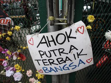 Poster bertuliskan dukungan untuk Basuki Tjahaja Purnama (Ahok) terpasang di pagar halaman Rutan Cipinang, Jakarta, Rabu (10/5). Poster dan karangan bunga terus berdatangan, meski Ahok sudah dipindahkan ke Rutan Mako Brimob. (Liputan6.com/Faizal Fanani)