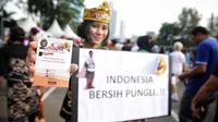 Satgas saber pungli menunjukkan buku imbauan saat mensosialisasikan tolak pungli di Car Free Day, Jakarta, Minggu (12/11). Satuan tugas sapu bersih pungutan liar (saber pungli) terus gencar melakukan sosialisasi anti pungli. (Liputan6.com/Faizal Fanani)