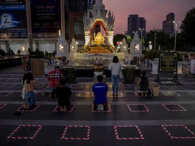 Umat berdoa di dalam area yang ditandai untuk jarak sosial di sebuah kuil untuk dewa Hindu Ganesh, di luar pusat perbelanjaan di Bangkok, Thailand, Selasa (29/12/2020). Thailand mengumumkan kematian pertamanya akibat virus corona COVID-19 sejak November. (AP Photo/Gemunu Amarasinghe)