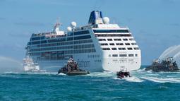 Kapal patroli menyemprotkan meriam air saat keberangkatan kapal pesiar milik Carnival, Adonia menuju Kuba dari Miami, Florida, Minggu (1/5). Perjalanan The Adonia ini merupakan yang pertama kali dilakukan setelah 50 tahun terakhir (Gaston De CARDENAS/AFP)