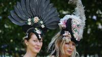 Dua wanita memakai hiasan kepala berpose saat tiba untuk menyaksikan balap kuda Royal Ascot horse di Ascot, London, (20/6). Mereka tampil gaya saat menyaksikan kompetisi balap kuda ini. (AFP Photo/Daniel Leal-Olivas)