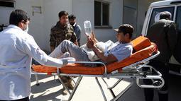 Seorang pria muda ditandu ke rumah sakit setelah serangan bom bunuh diri di dekat Universitas Kabul, Afghanistan, (21/3). Sedikitnya 26 orang tewas akibat serangan bom bunuh diri saat perayaan tahun baru Persia. (AP Photo/Rahmat Gul)
