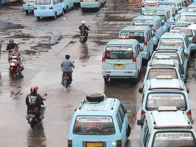 Pengendara sepeda motor melintasi jalur angkutan umum di Terminal Kampung Melayu, Jakarta, Rabu (6/2). Meskipun terdapat larangan melintas bagi pemotor, namun masih ada sejumlah pengendara nekat menerobos masuk terminal. (Liputan6.com/Immanuel Antonius)