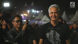 Gubernur Jawa Tengah, Ganjar Pranowo tiba untuk menonton Jogjarockarta 2018 di Stadion Kridosono Yogyakarta (27/10). Ganjar tampil seperti anak metal lainnya dengan pakaian hitam dan celana jeans. (Fimela.com/Bambang E.Ros)
