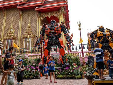 Suasana di depan kuil Buddha Wat Tha Kien yang menghadirkan patung logam raksasa yang terinspirasi oleh 'Transformers' di Nonthaburi, Thailand (18/6). Patung karya Ban Hun Lek dihadirkan untuk menarik pengunjung. (AFP Photo/Lillian Suwanrumpha)