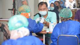 Petugas kesehatan mengambil sampel darah anggota KPPS saat rapid test Covid-19 di kantor Kelurahan Pondok Benda, Tangerang Selatan, Jumat (27/11/2020). Rapid test dilakukan guna mengantisipasi penyebaran Covid-19 saat pemungutan suara Pilkada Kota Tangerang Selatan 2020. (merdeka.com/Dwi Narwoko)